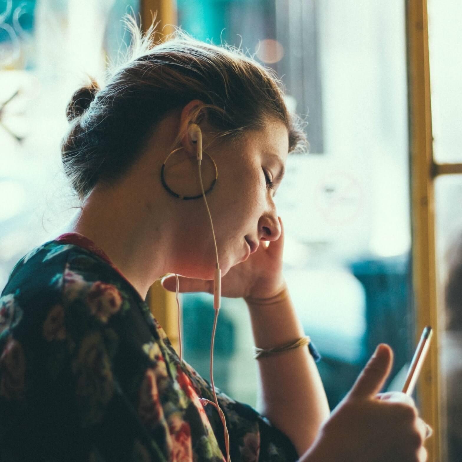 Nainen kuuntelemassa miksausta kuulokkeilla